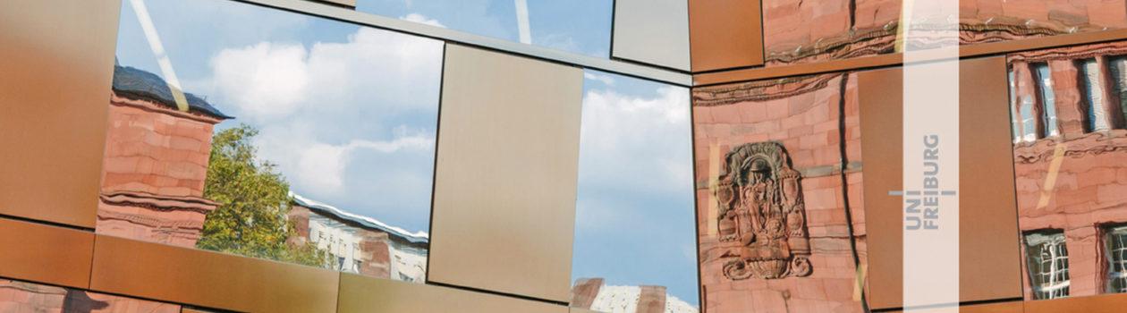Im Spiegel der Fensterscheiben der modernen Universitätsbibliothek erscheint das traditionell aus Sandstein gebaute Kollegiengebäude I.